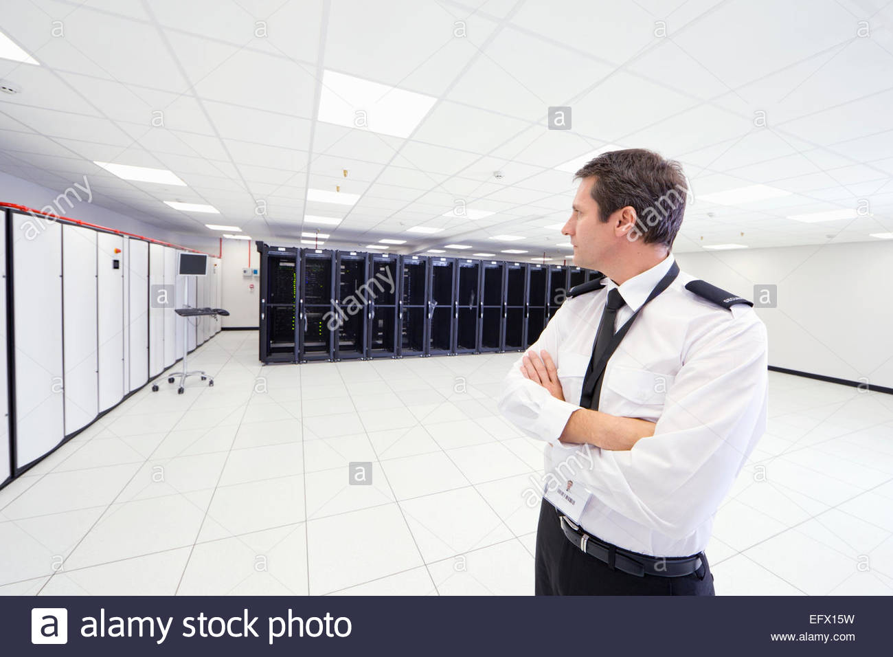 Security guard standing with arms crossed in server room - Stock Image