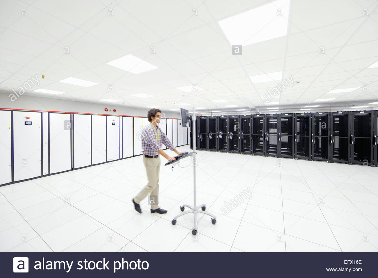 Technician walking through server room with portable computer - Stock Image