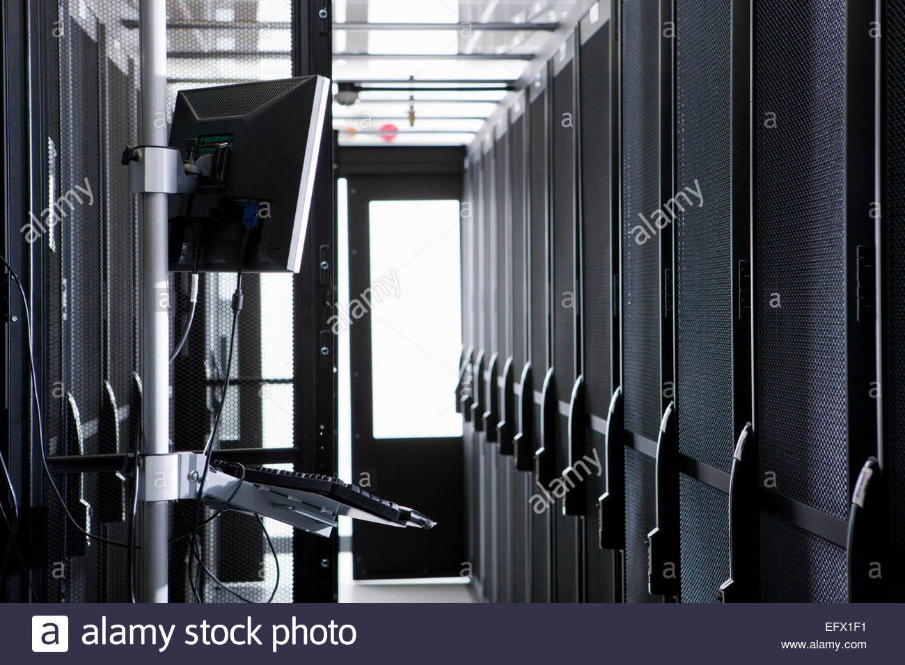 Portable computer in aisle of server storage cabinets - Stock Image