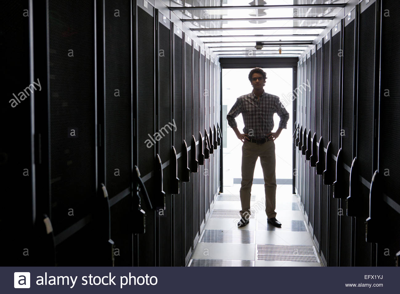Technician standing in aisle of storage cabinets in data center - Stock Image