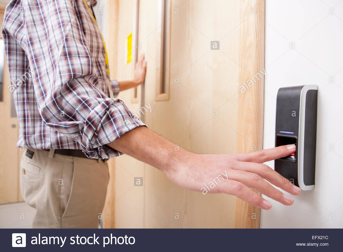 Man using finger print entry technology to open door - Stock Image