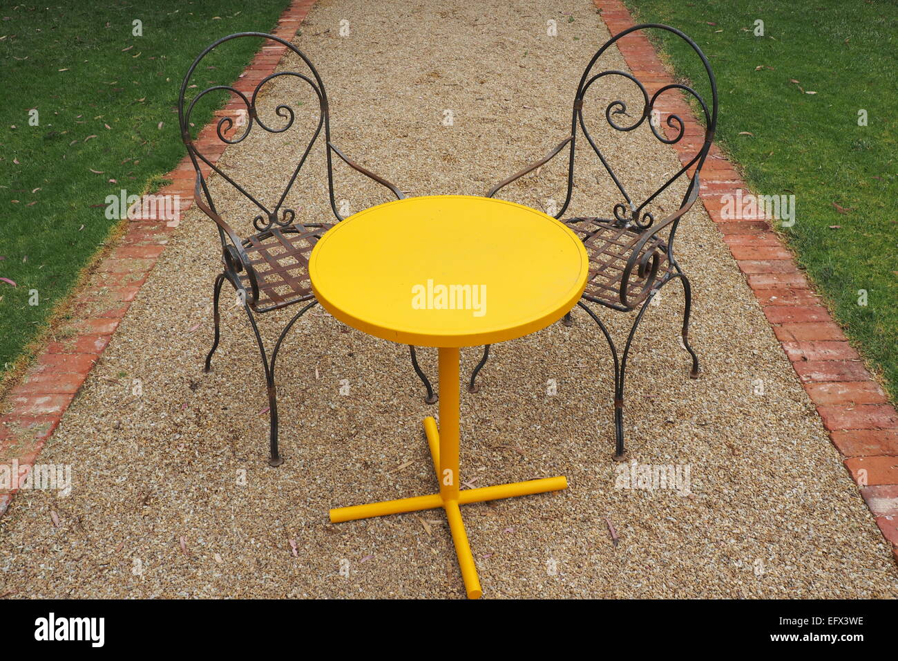 A round yellow table and two metal chairs in a garden Stock Photo