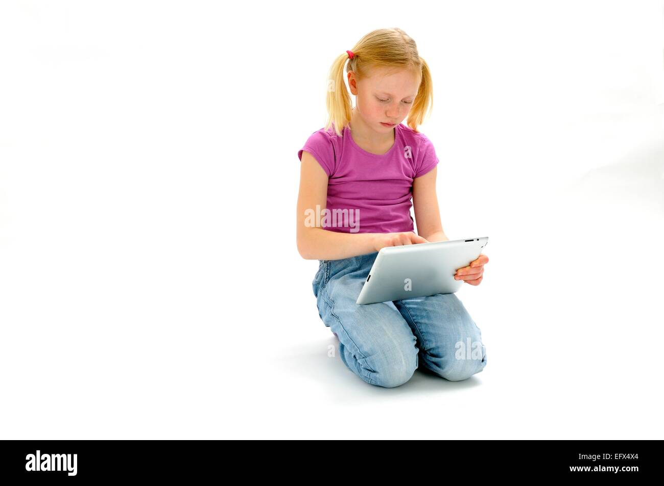 Young girl working on tablet computer - Stock Image