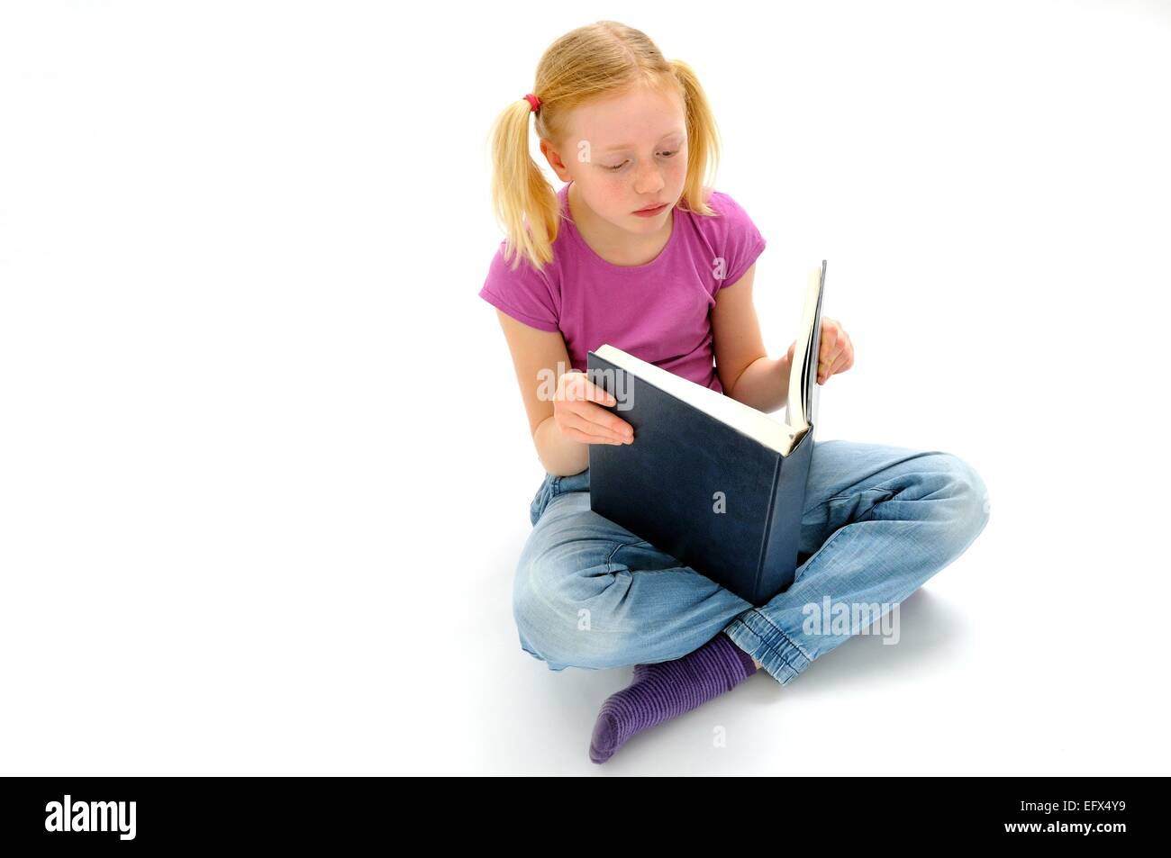 Pre teen girl reading a large book - Stock Image