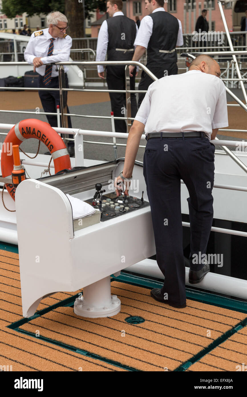 Officer docking a river cruise ship by using outboard-mounted thruster control panel. - Stock Image