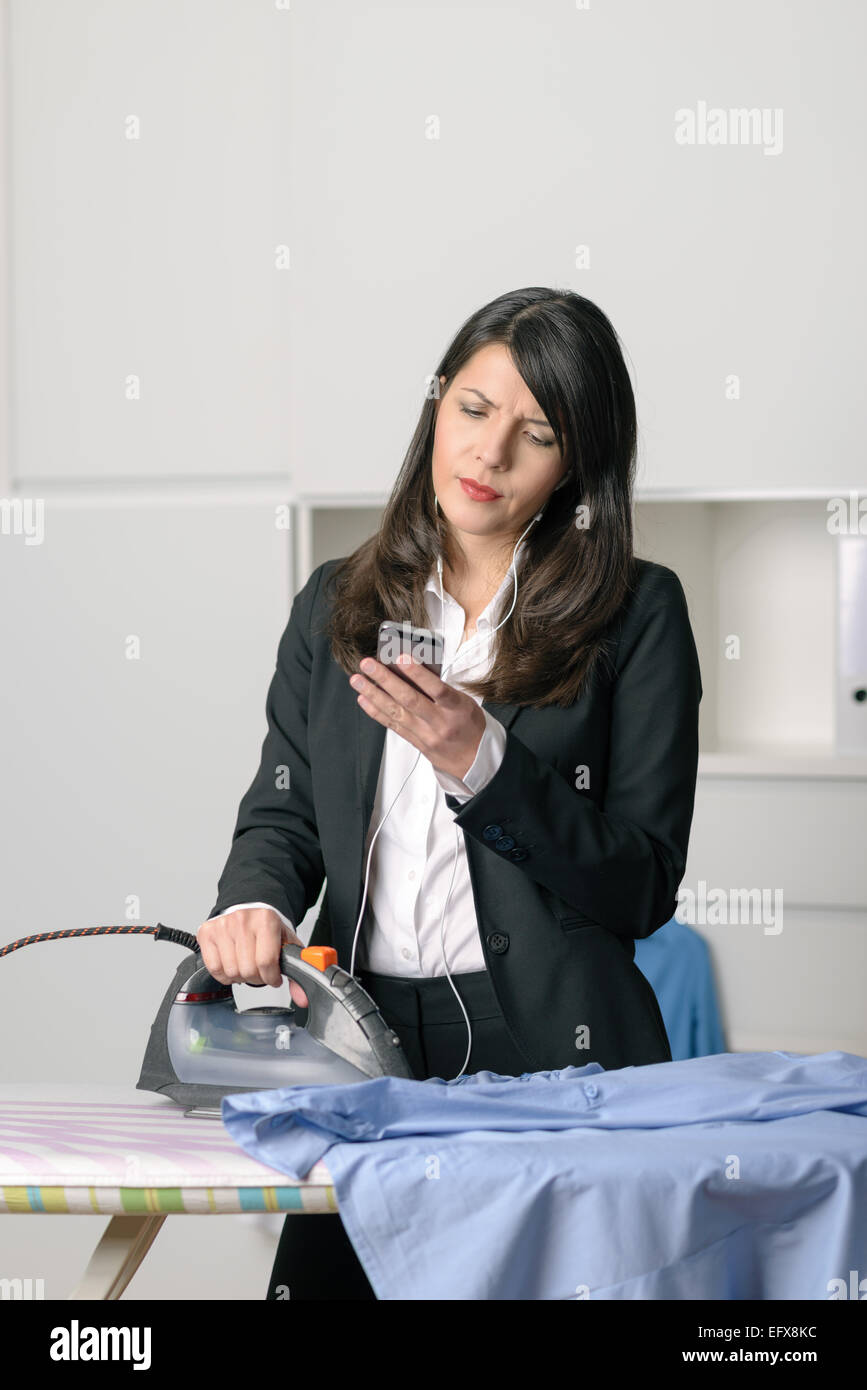 Bored unhappy housewife doing the ironing staring off to the side with a glum expression while simultaneously checking - Stock Image
