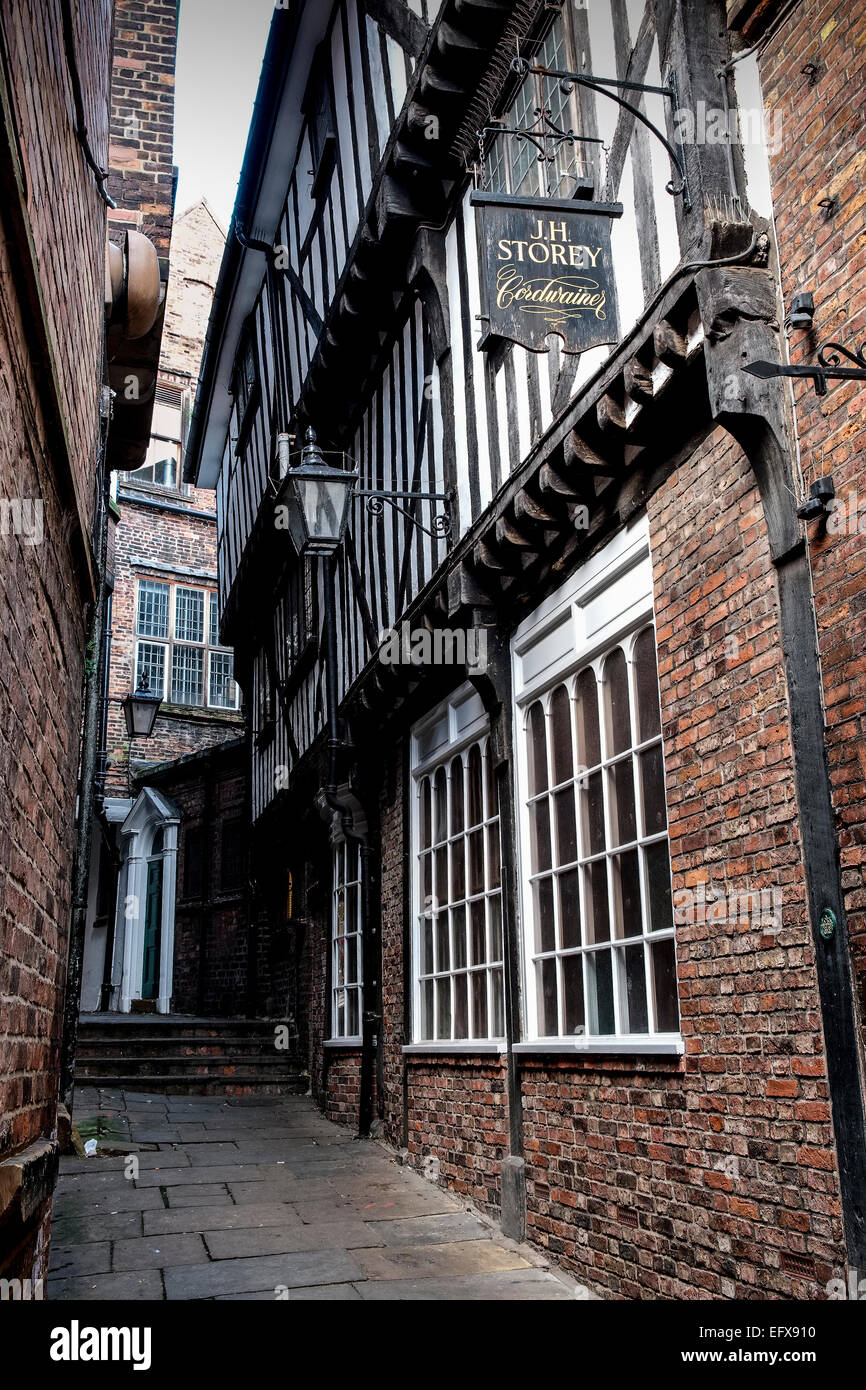 Lady Peckett's Yard, York, UK. An old sign for a cordwainer (shoemaker) is high up on a wall in a narrow alley. Stock Photo