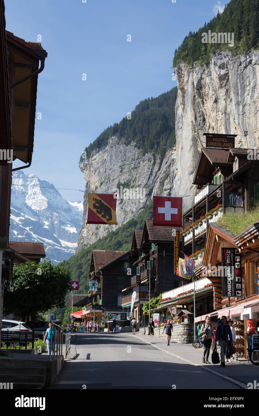 Visitors walk among shops and businesses that line streets in the municipality of Lauterbrunnen in the Swiss Alps - Stock Image