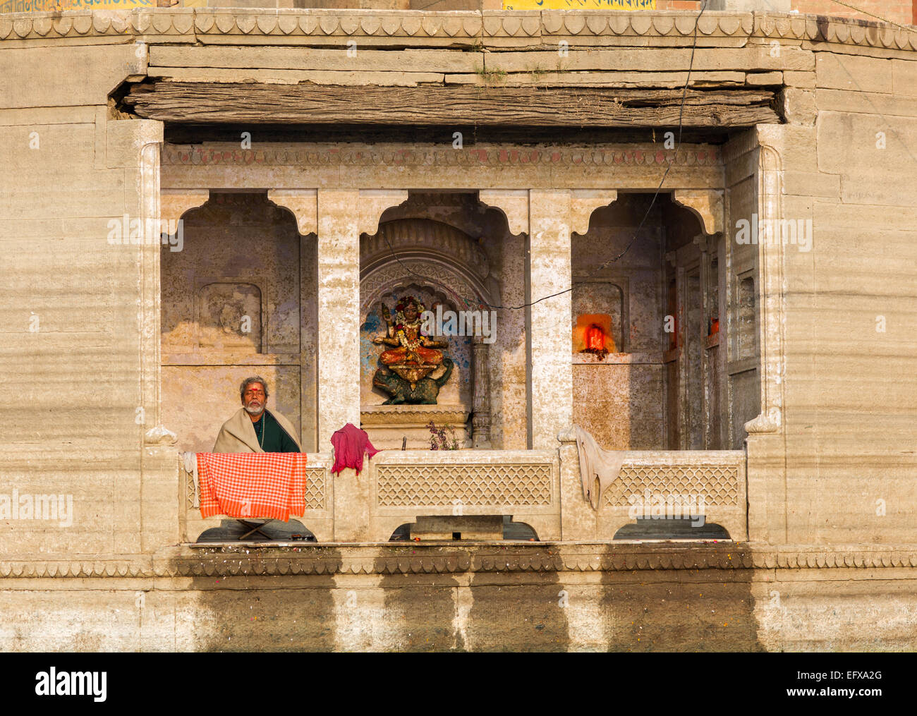In deep meditation absorbed Hindu on a balkony of a palace at the riverbank of the Ganges Stock Photo