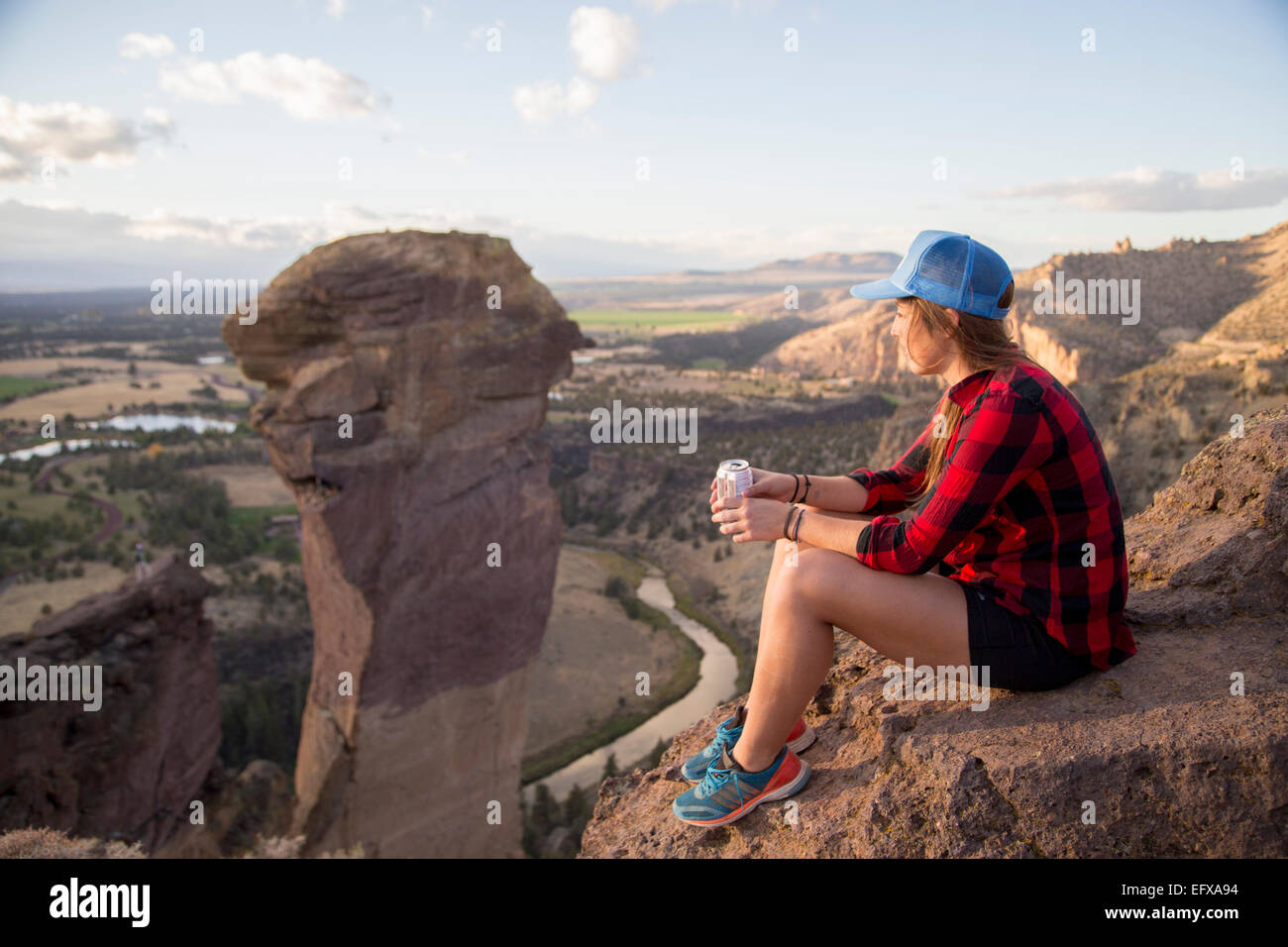Young woman sitting gazing at view from top of Smith Rock, Oregon, USA - Stock Image