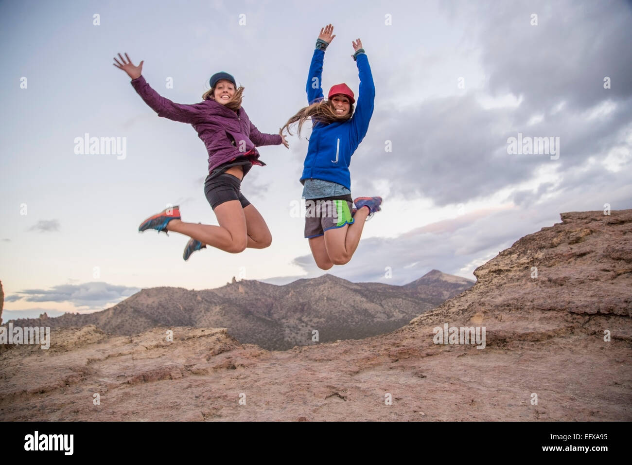 Two young female climbers jumping mid air on top of Smith Rock, Oregon, USA - Stock Image