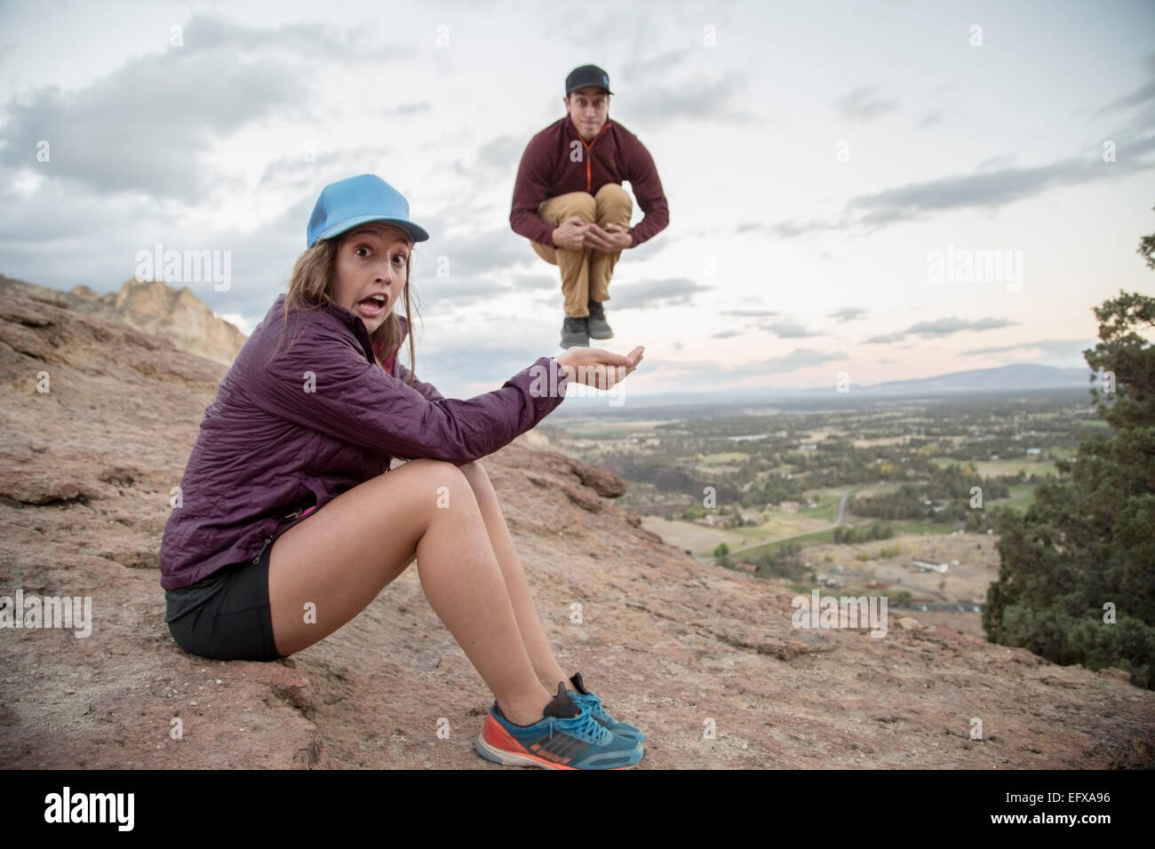 Young man jumping mid air on top young womans hand,  Smith Rock, Oregon, USA - Stock Image