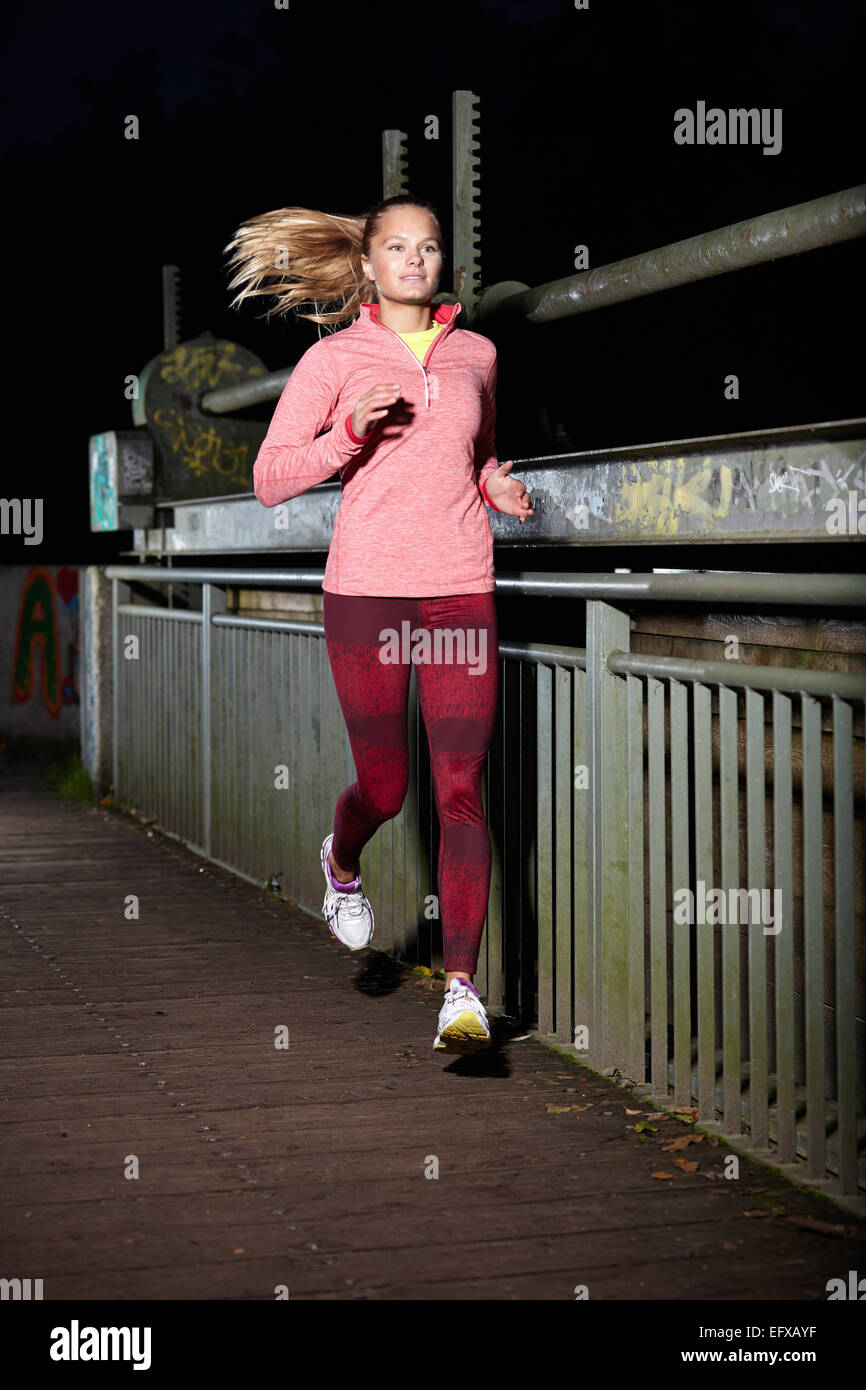 Young woman running on footbridge at night - Stock Image