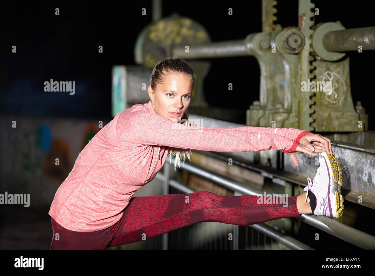 Young woman touching toes on footbridge at night - Stock Image