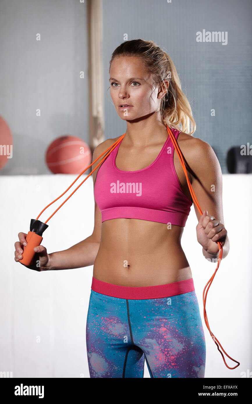 Portrait of young woman with skipping rope on shoulders in gym - Stock Image