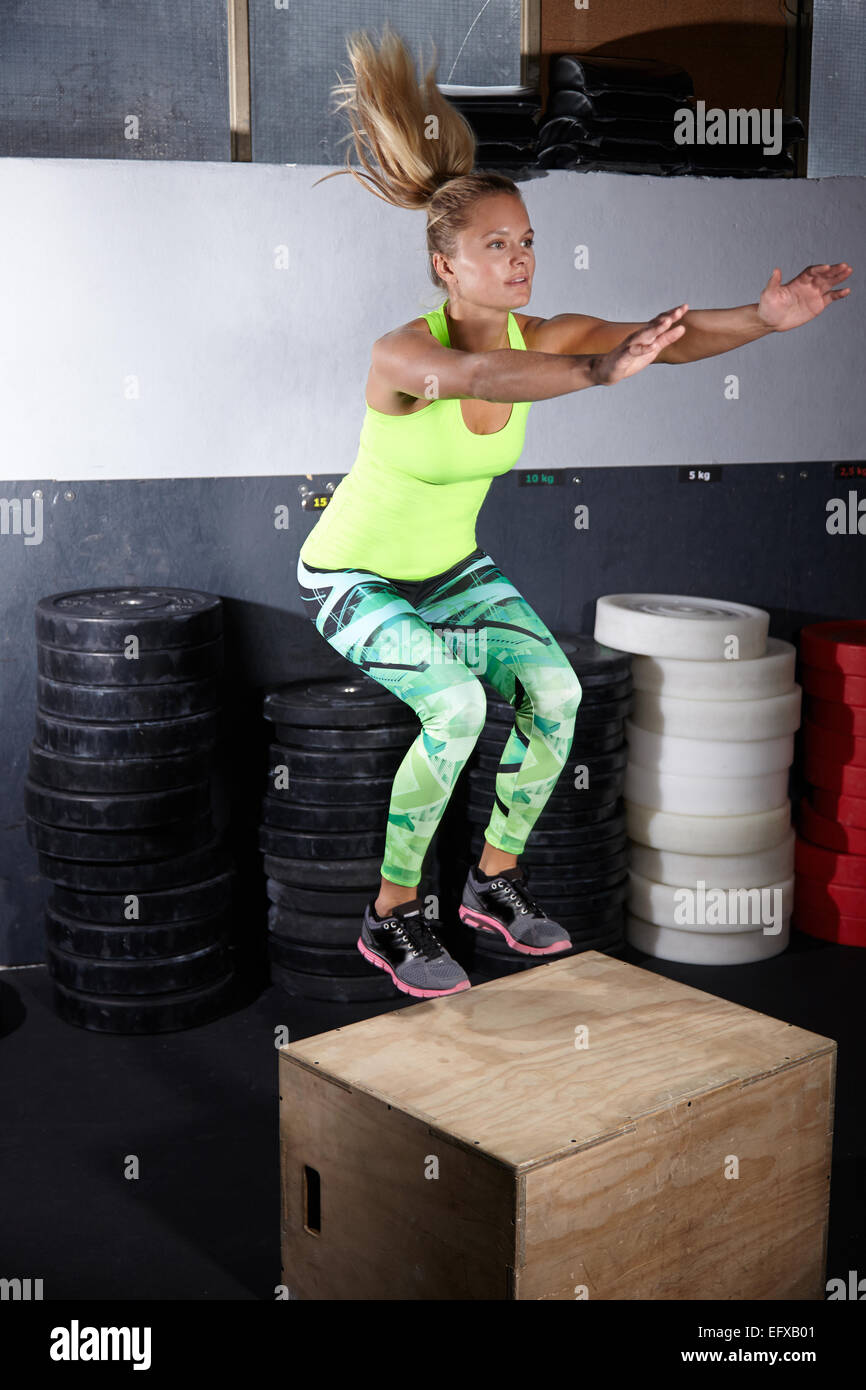 Young woman jumping onto box in gym - Stock Image