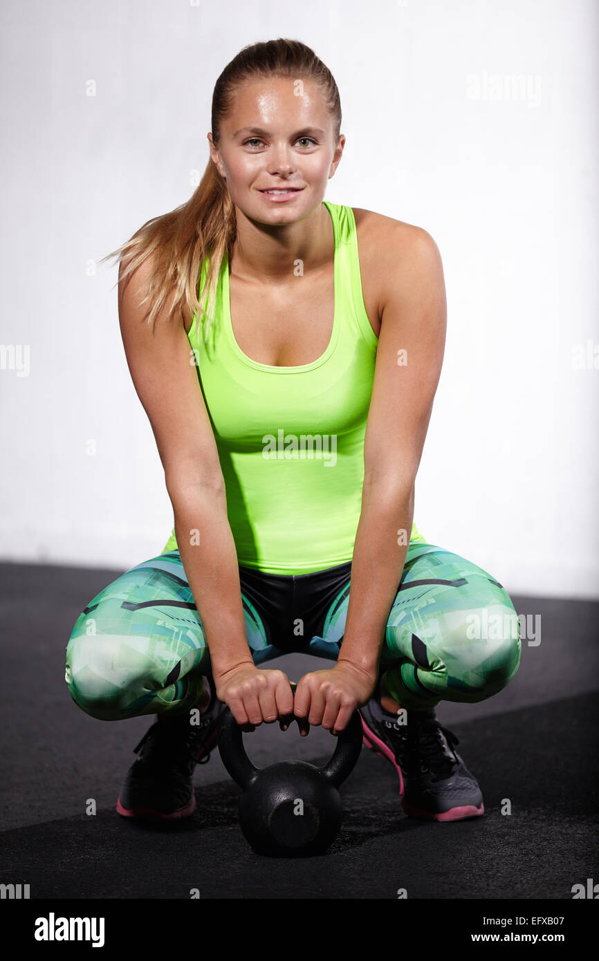 Portrait of young woman crouching with kettle bell in gym Stock Photo