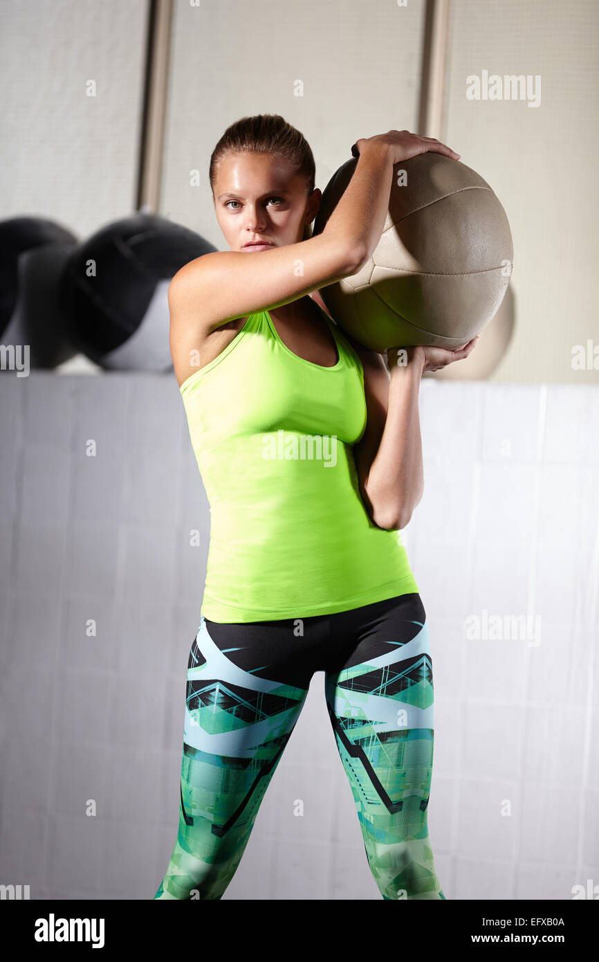 Portrait of young woman holding up exercise ball in gym - Stock Image