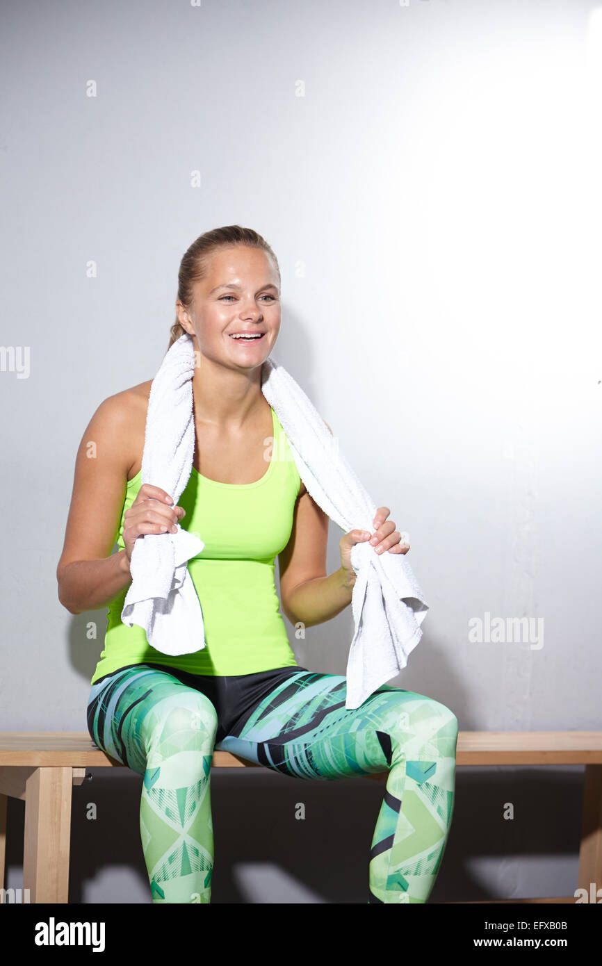 Young woman sitting on bench taking a break in gym - Stock Image