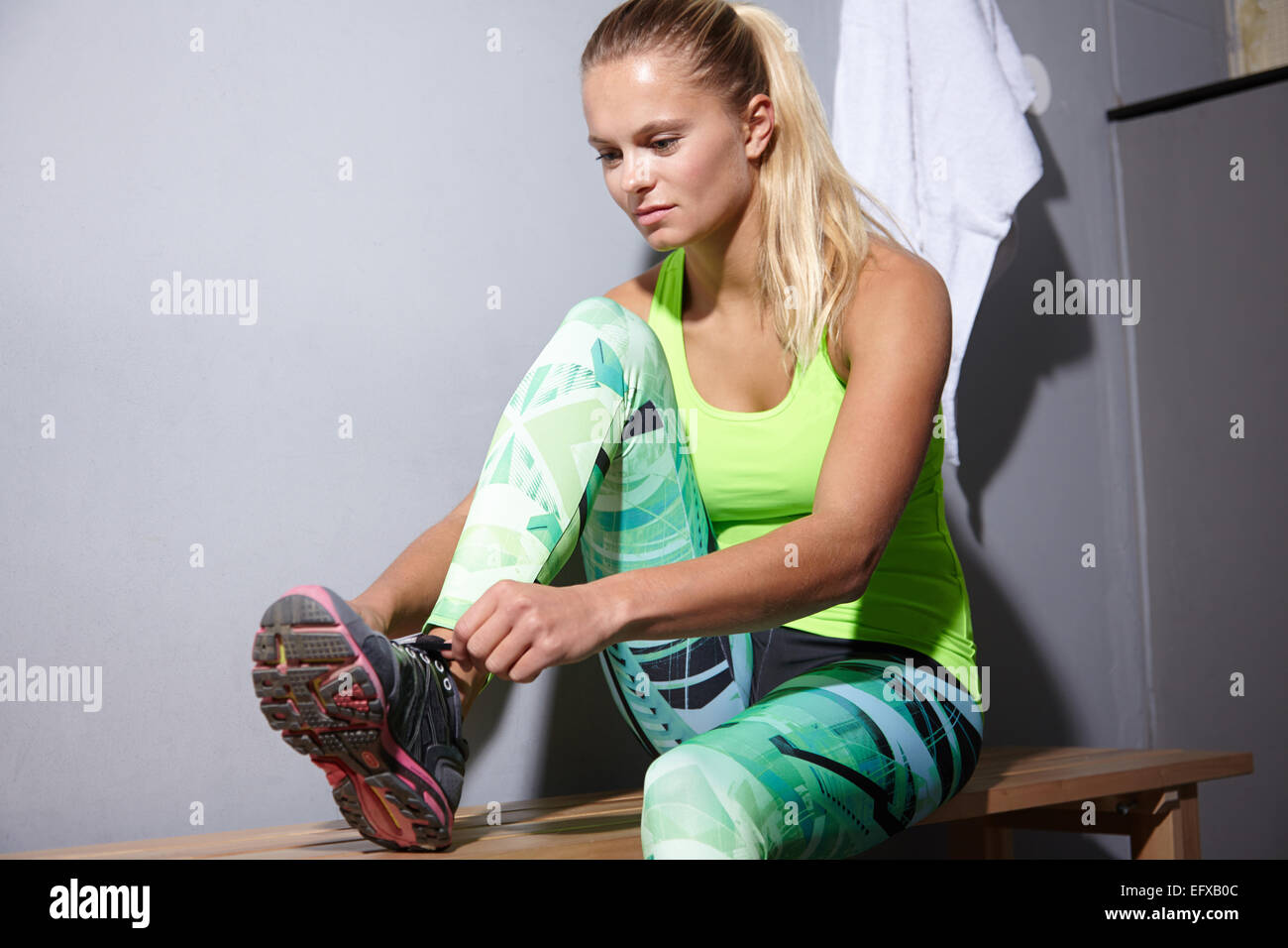 Portrait of young woman tying trainer laces in gym - Stock Image
