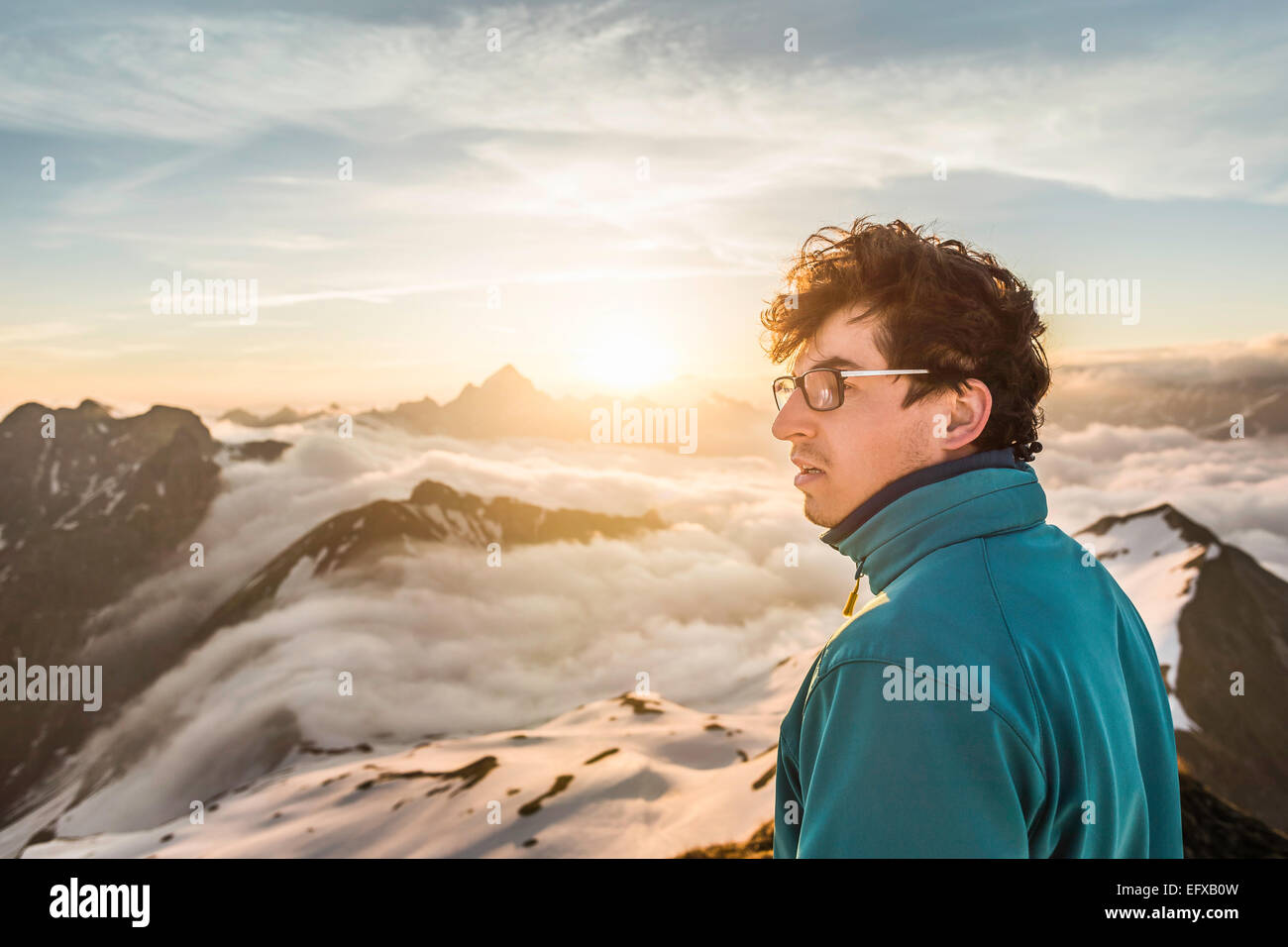 Young male mountain trekker looking at view above clouds, Bavarian Alps, Oberstdorf, Bavaria, Germany - Stock Image