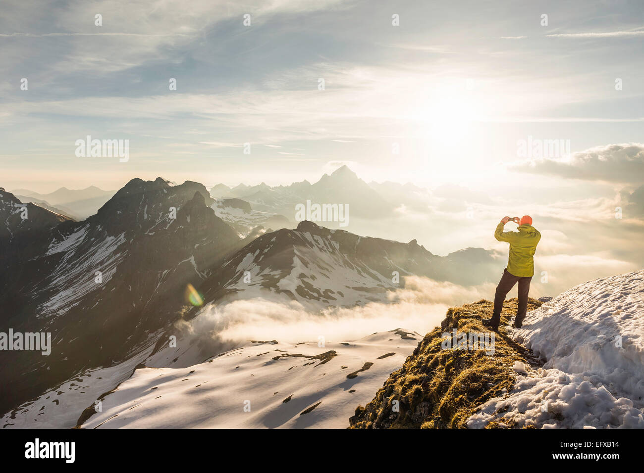 Young male mountain trekker photographing view of clouds, Bavarian Alps, Oberstdorf, Bavaria, Germany - Stock Image