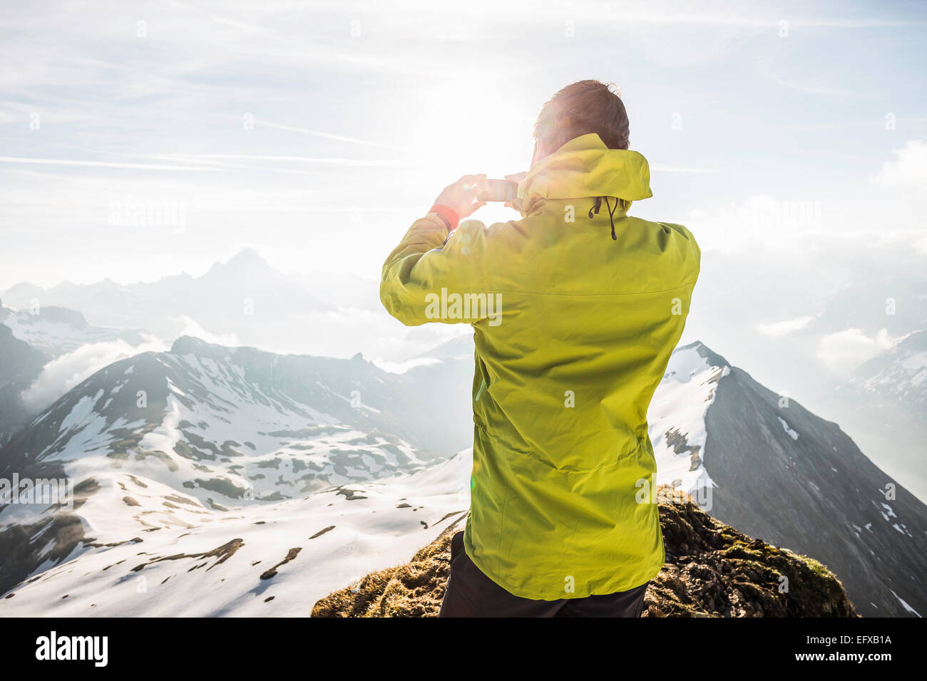 Young male mountain trekker photographing Bavarian Alps, Oberstdorf, Bavaria, Germany - Stock Image