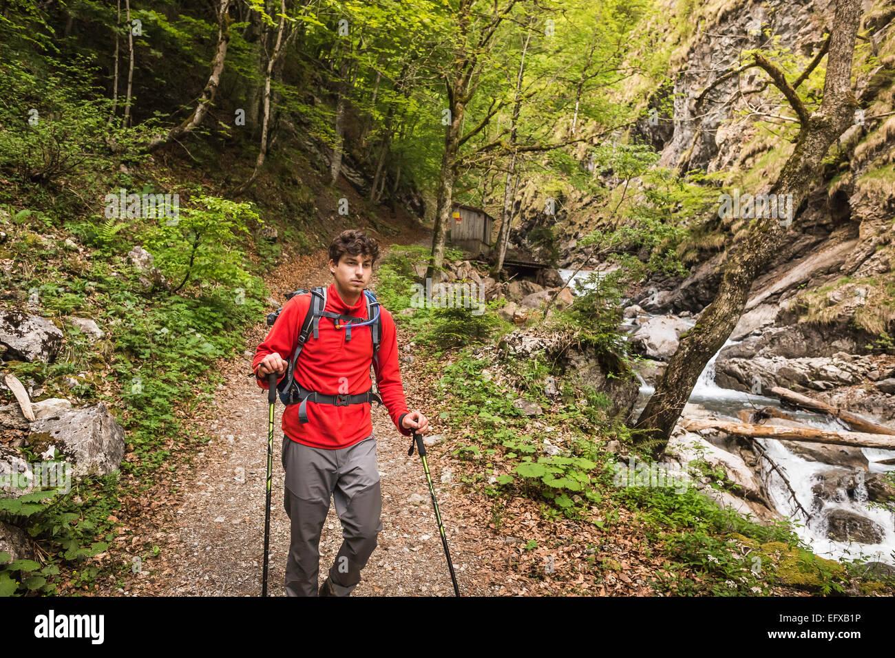 Young man hiking on river path, Oberstdorf, Bavaria, Germany Stock Photo