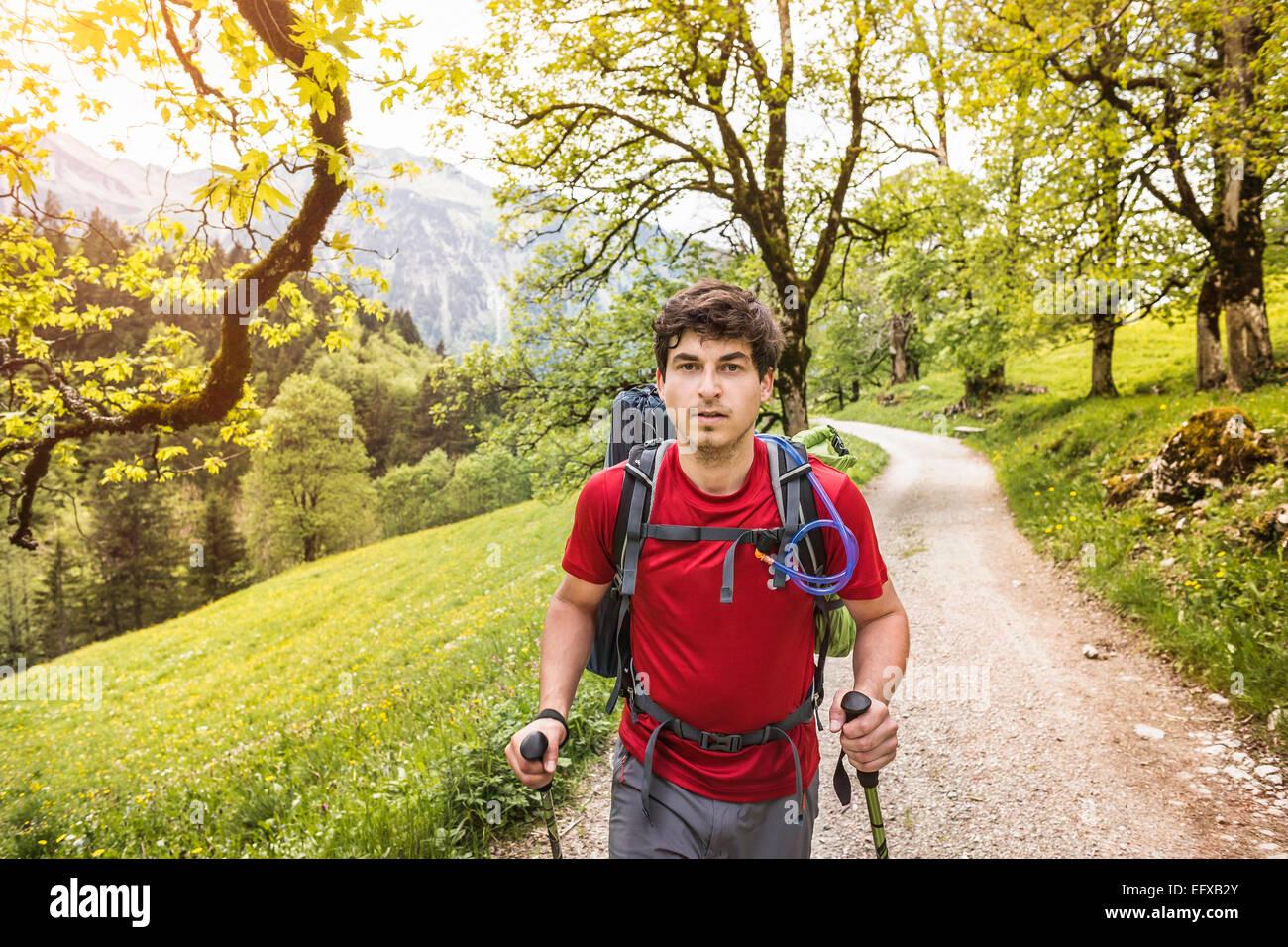 Young man hiking up rural road, Oberstdorf, Bavaria, Germany - Stock Image