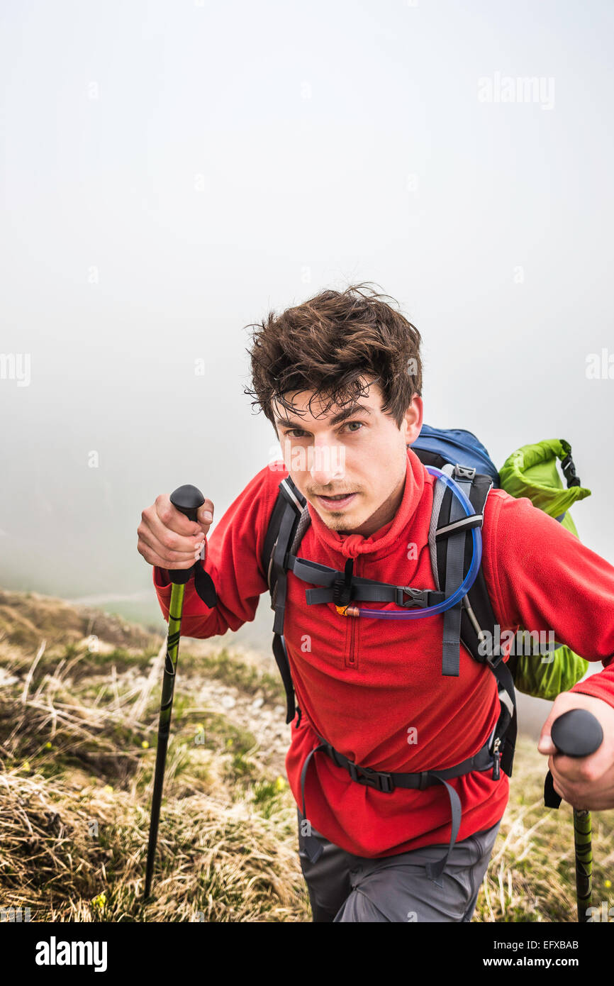 Portrait of young man mountain trekking in mist, Bavarian Alps, Oberstdorf, Bavaria, Germany - Stock Image