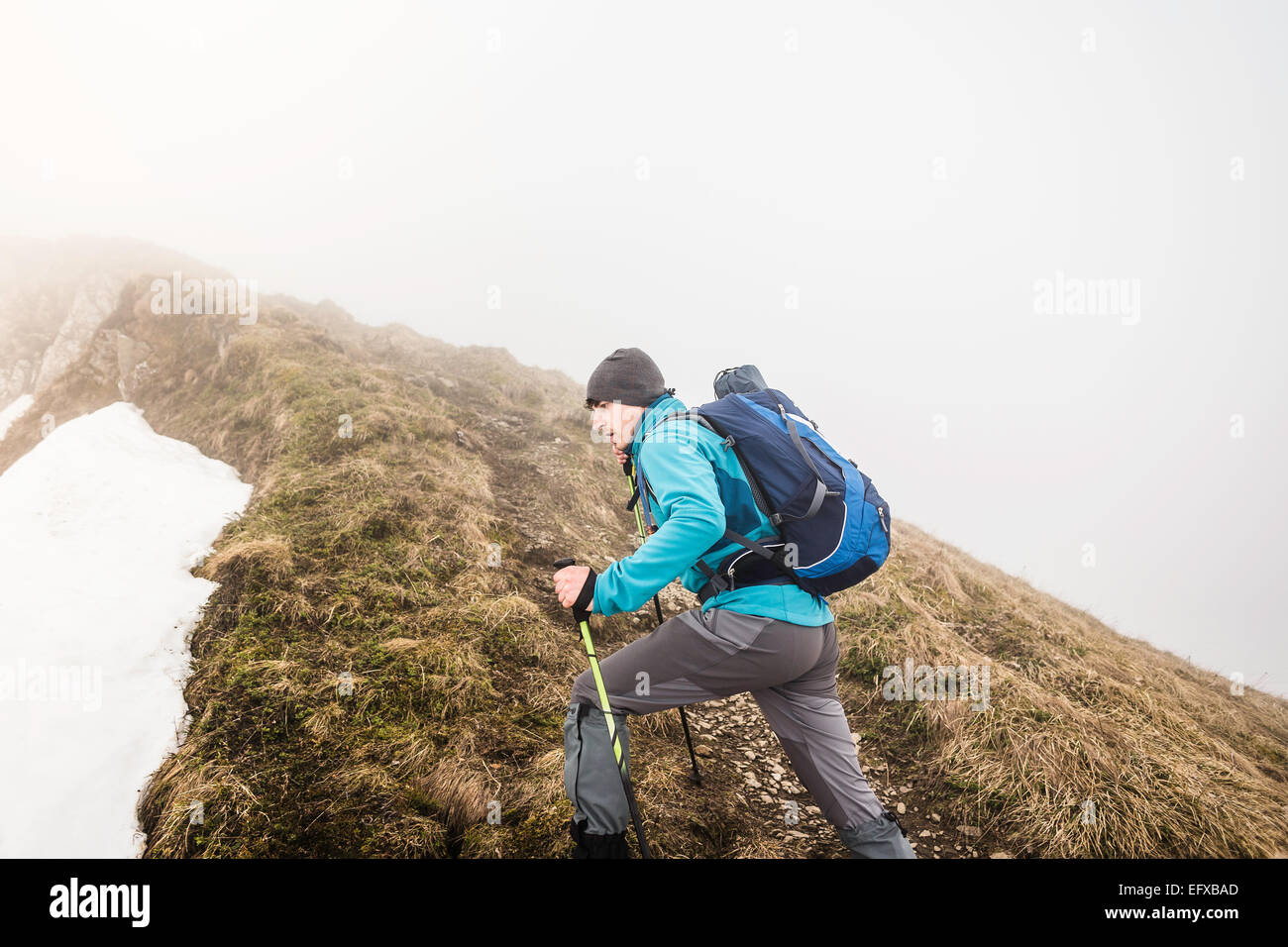 Young man mountain trekking in snow and mist, Bavarian Alps, Oberstdorf, Bavaria, Germany - Stock Image