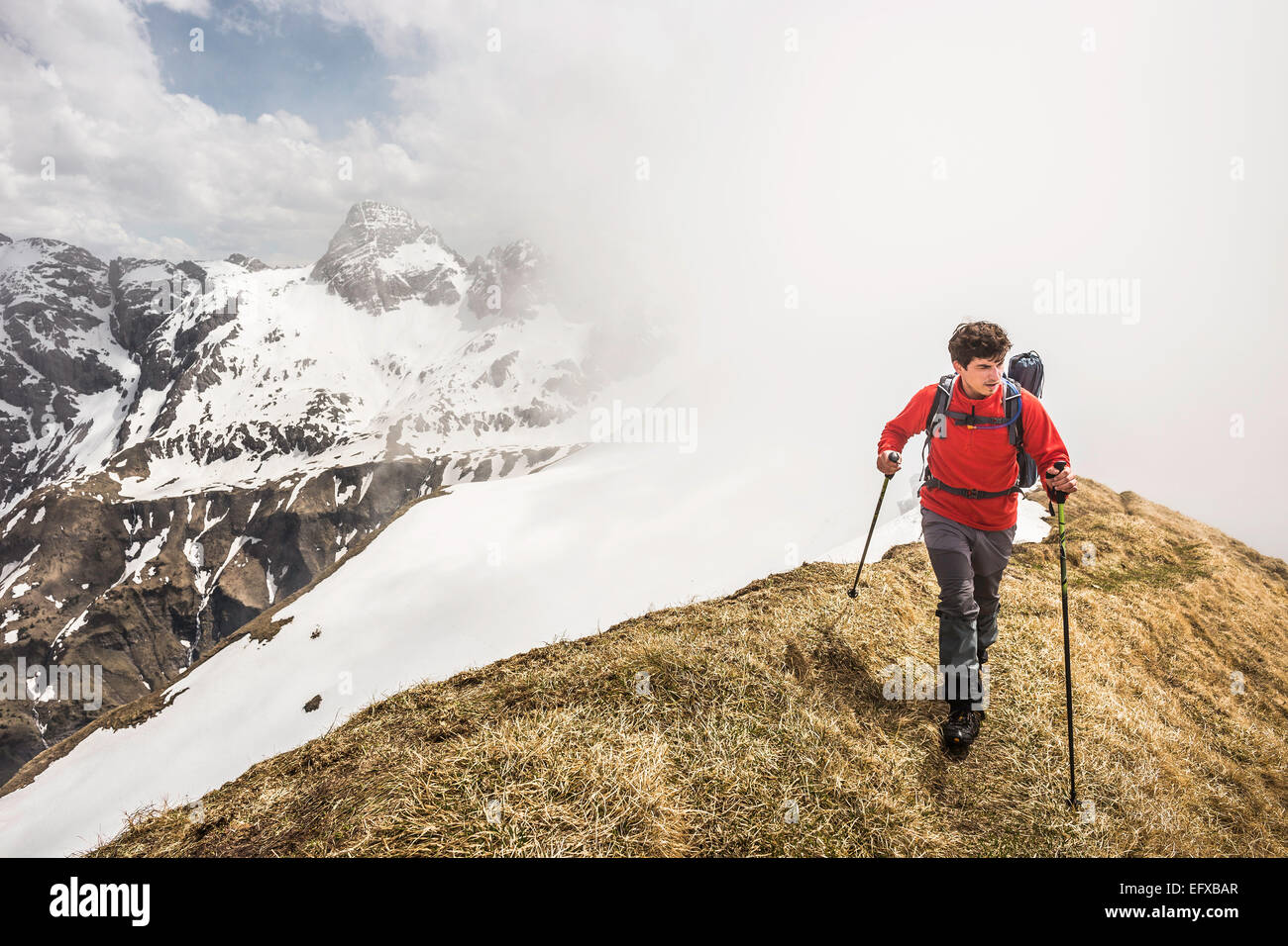 Young man mountain trekking along ridge in Bavarian Alps, Oberstdorf, Bavaria, Germany - Stock Image