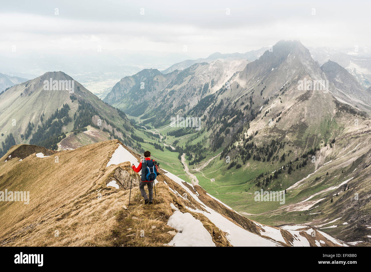 Young man mountain trekking down ridge in Bavarian Alps, Oberstdorf, Bavaria, Germany - Stock Image