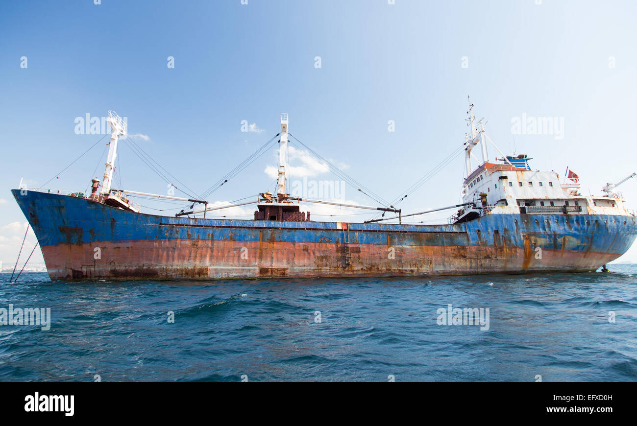 A Rusty Cargo Ship is anchored in Sea - Stock Image