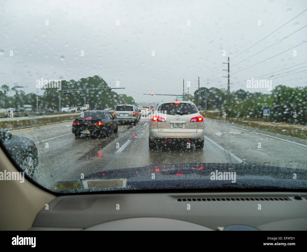 Traffic stopped at traffic light on a rainy overcast day - Stock Image