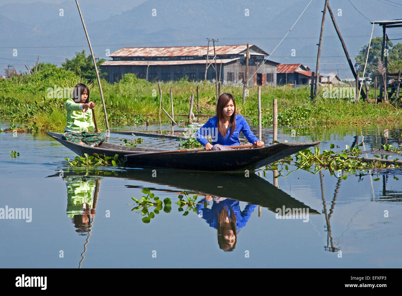 Two Intha women rowing in a traditional wooden open boat / pirogue / proa on Inle Lake, Nyaungshwe, Shan State, - Stock Image