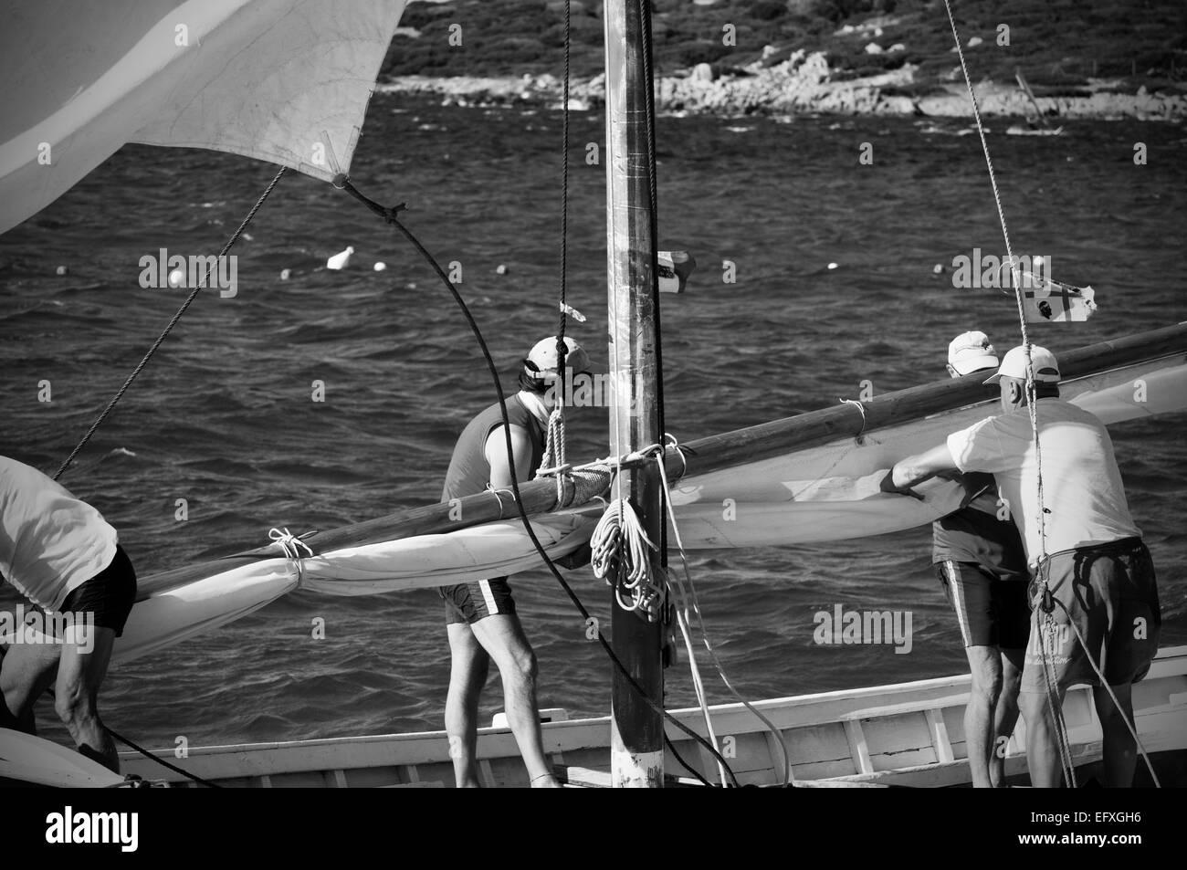 Crew working on board of an old Latin (Lateen) classic sail boat, sea of Palau, Gallura, north-east coast of Sardinia, - Stock Image