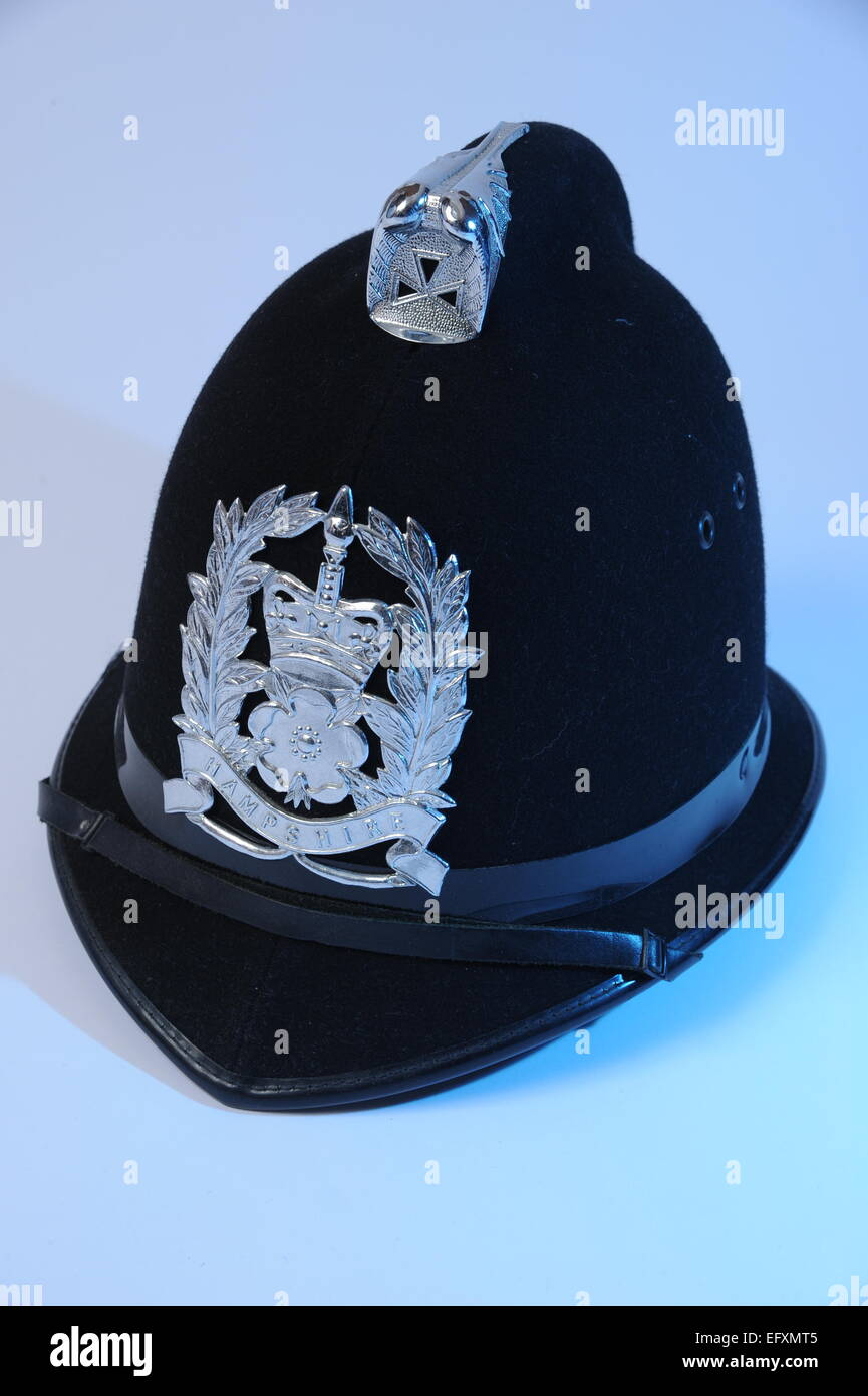 Policeman's uniform helmet with HAMPSHIRE police badge with blue fill light. - Stock Image