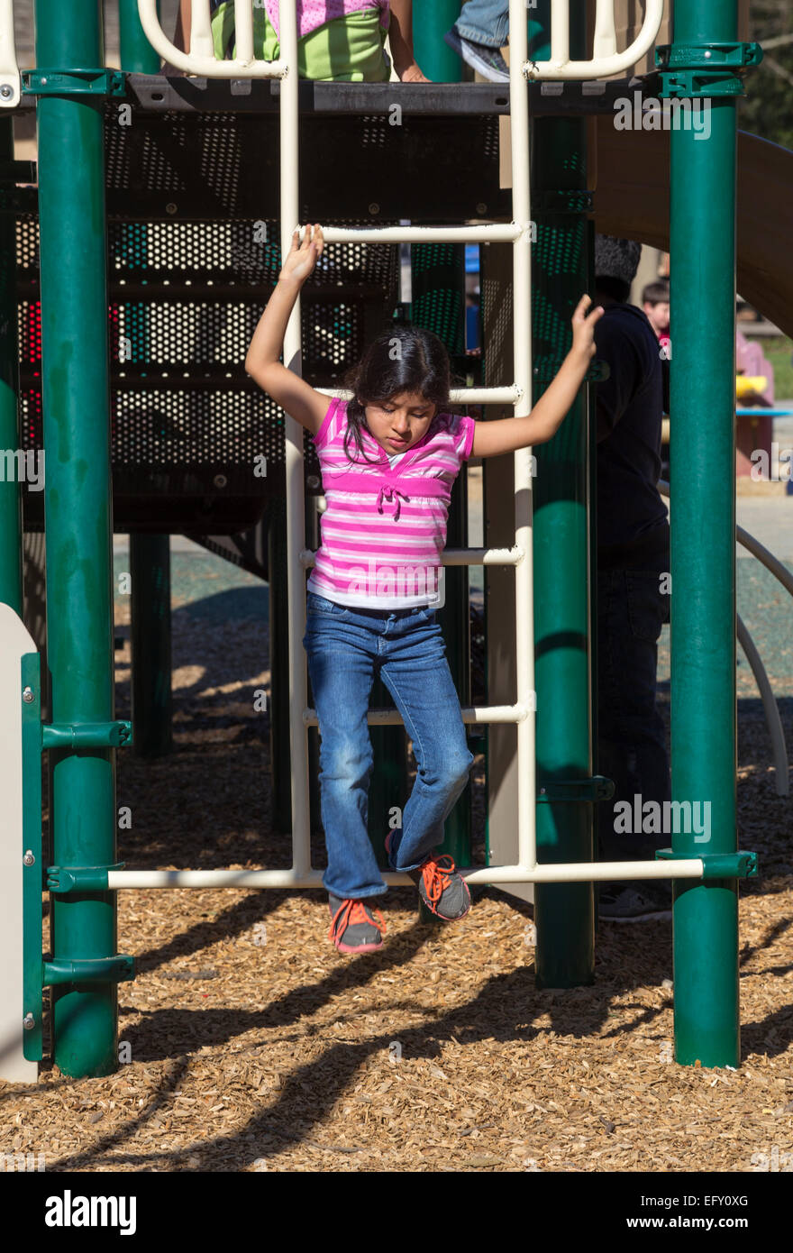 Hispanic girl, young girl, girl, climbing down ladder, playground, Pioneer Park, Novato, California - Stock Image
