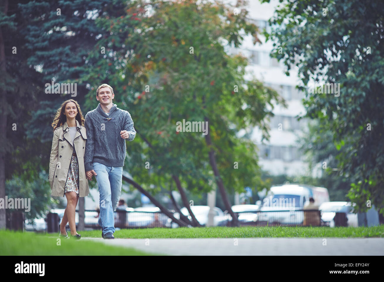Young dates in casualwear walking in park - Stock Image