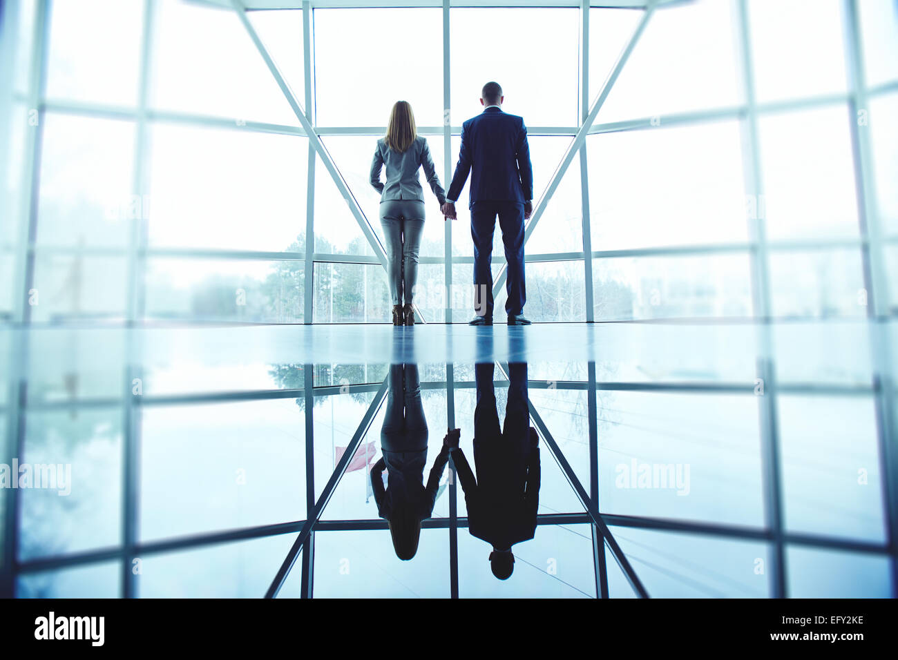 Young man and woman in formalwear holding by hands while standing by office window - Stock Image