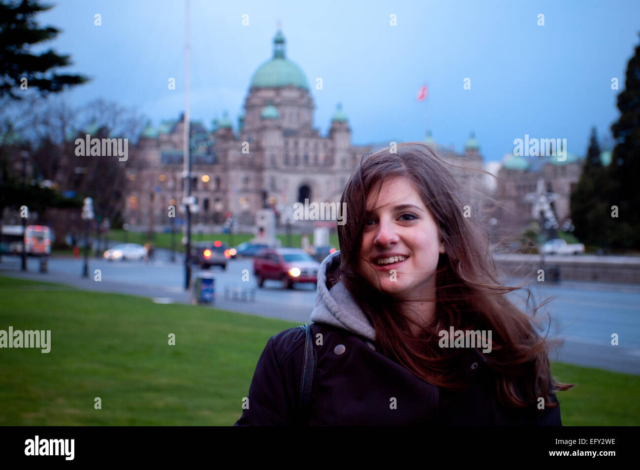 Pretty brunette girl on a rainy day in Victoria, British Columbia, Canada. The British Columbia Parliament is in - Stock Image
