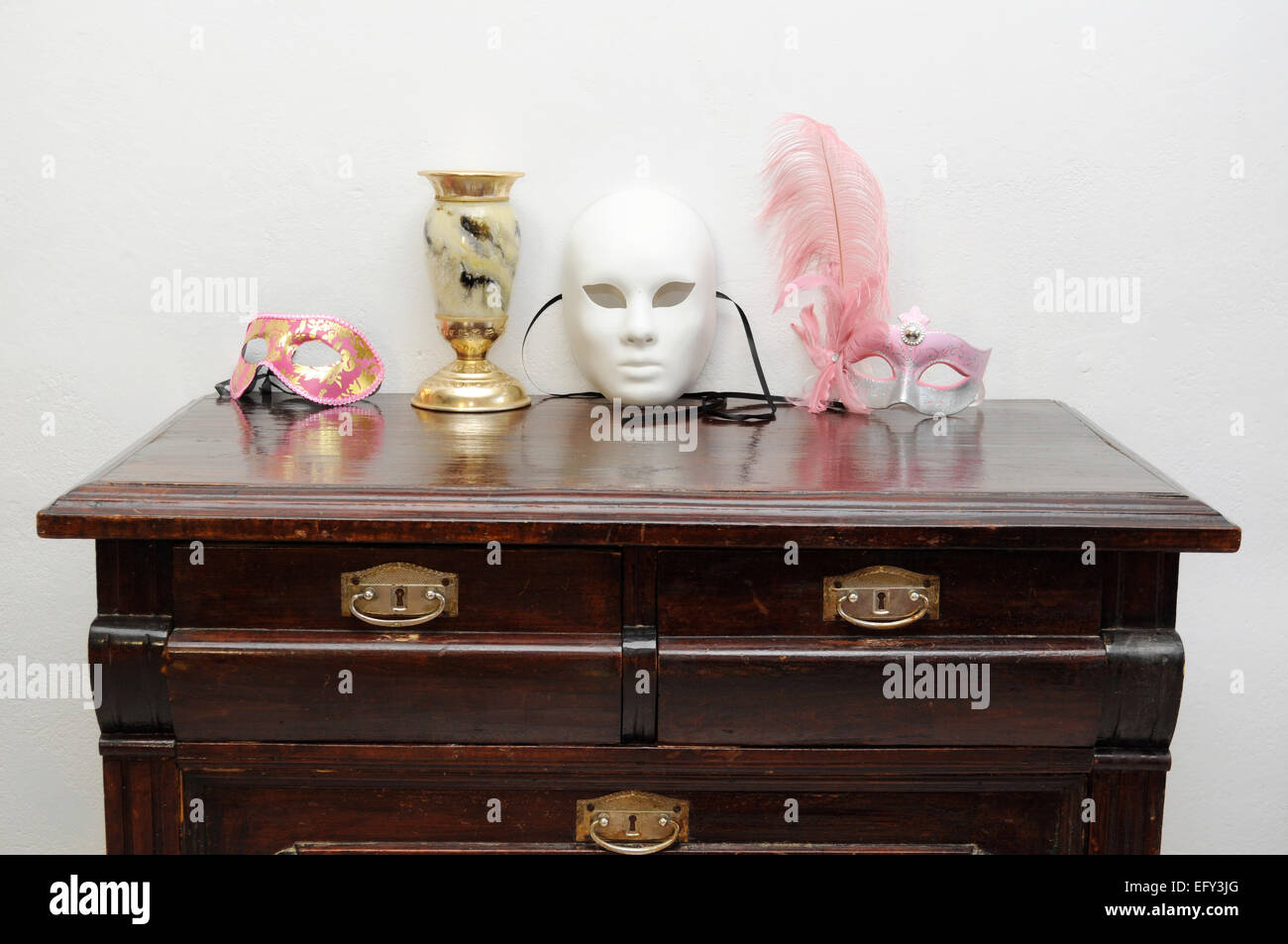 A Collection Of Masks And An Old Goblet On The Vintage Commode Stock