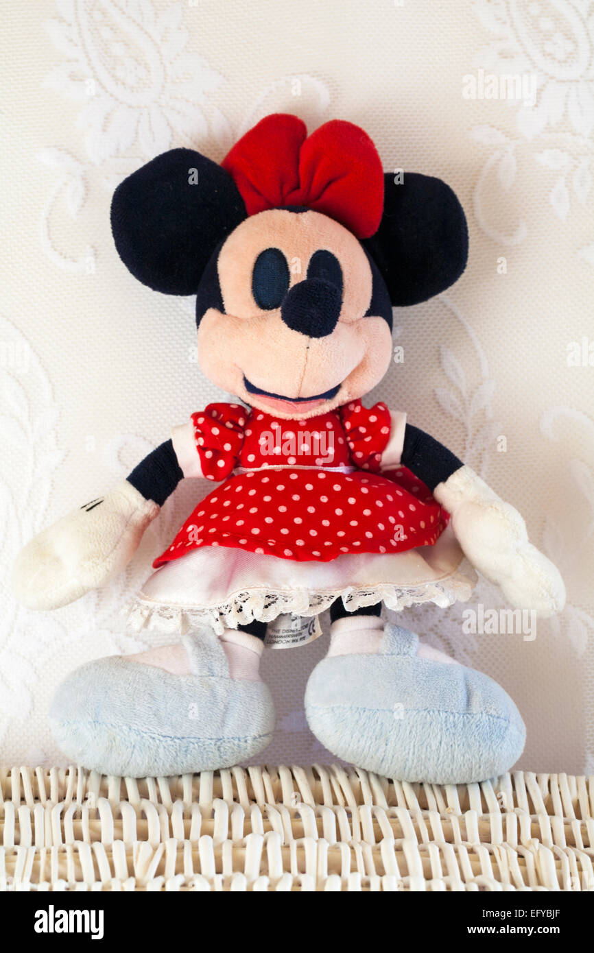 Minnie Mouse in red polka dot dress soft plush cuddly toy standing on wicker basket Stock Photo