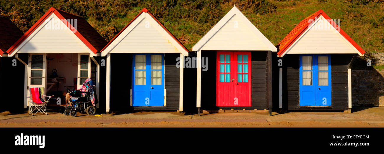 Wheelchair and colourful beach huts with blue and red doors in a row traditional English structure and shelter at - Stock Image