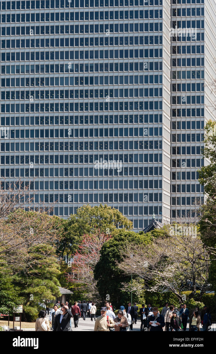 Tokyo, Japan. Towering office blocks overlook the East Gardens of the Imperial Palace Stock Photo
