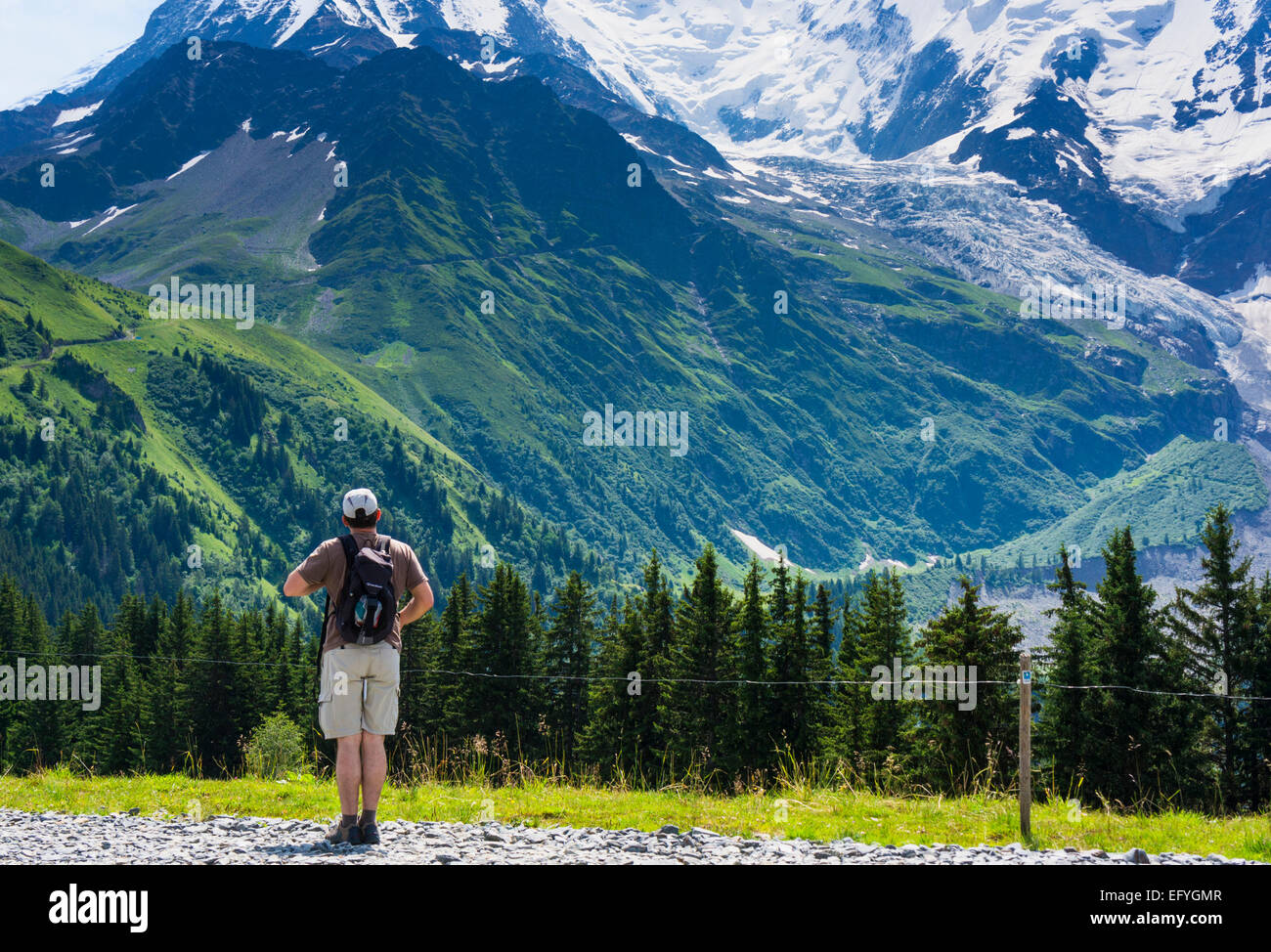 Walker walking and looking towards the lower slopes of Mont Blanc and the Glacier de Bionnassay, Chamonix, French - Stock Image