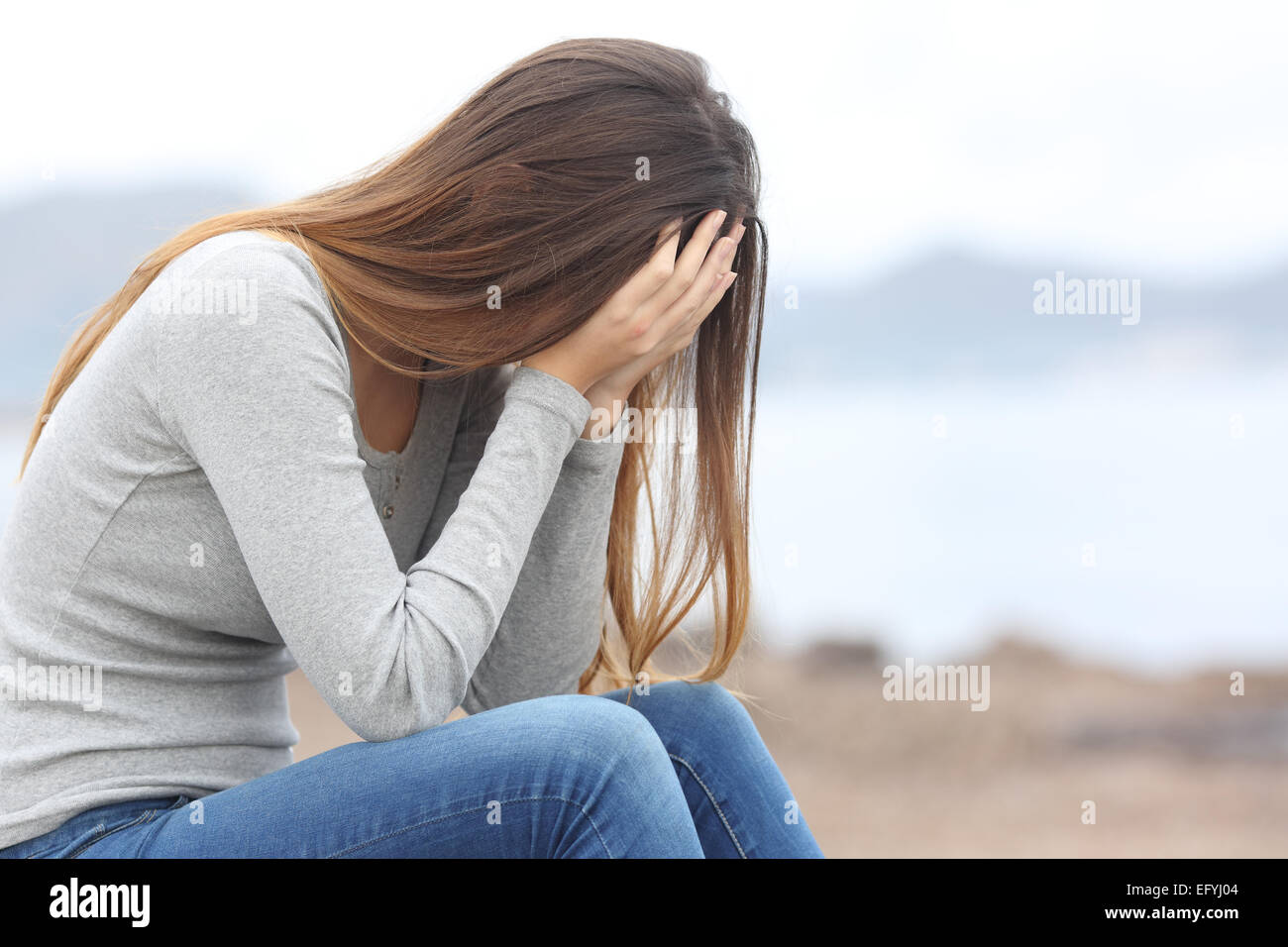 Worried teenager woman covering her face with hands on the beach in winter Stock Photo