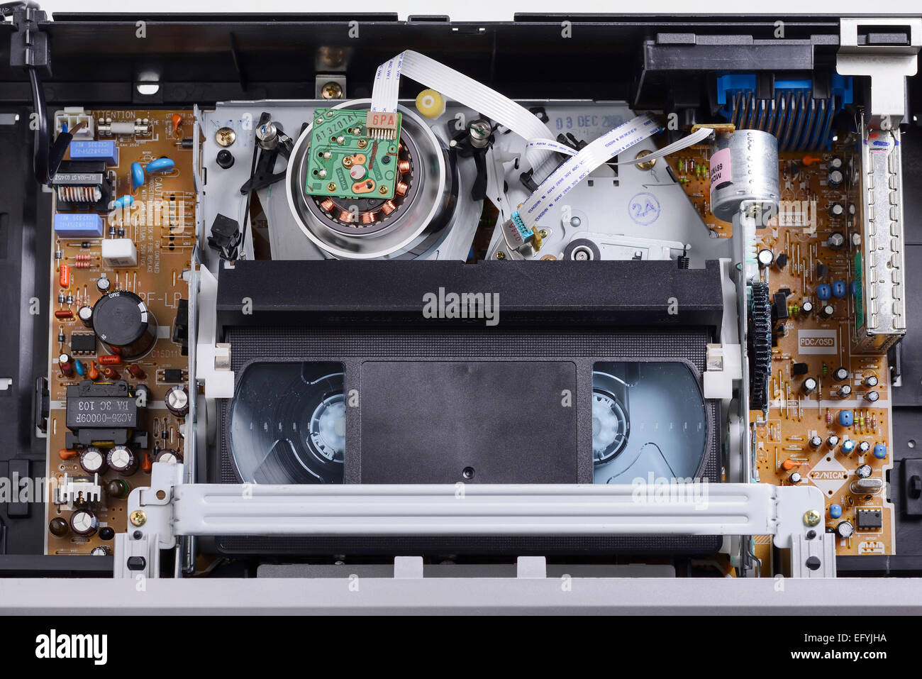 The inside of a VHS video cassette player with a tape laced around the playing head - Stock Image