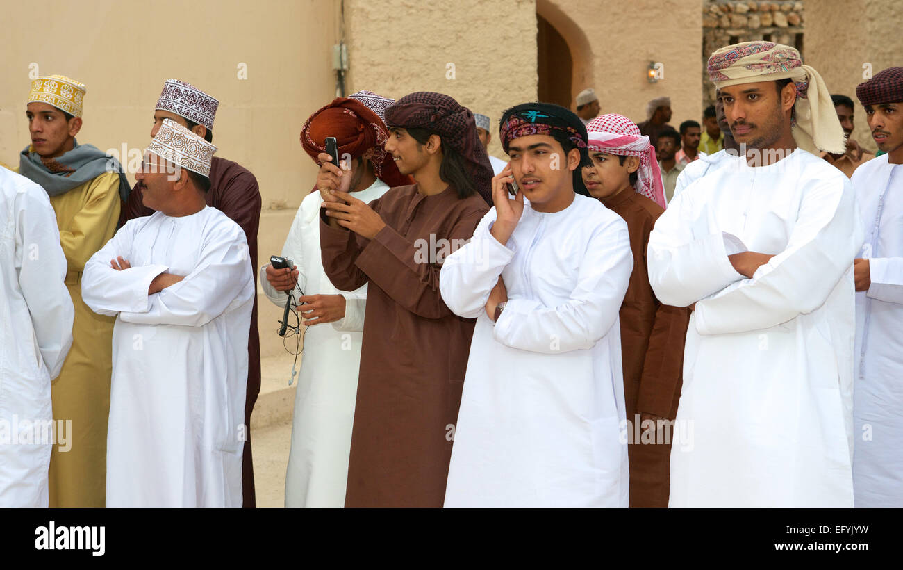 Omani men watching a tribal dance during the annual Muscat Festival, in the Sultanate of Oman. - Stock Image